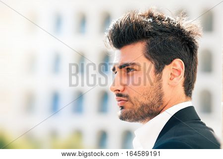 A young and handsome man is thinking about his future. Stylish hair and beard.