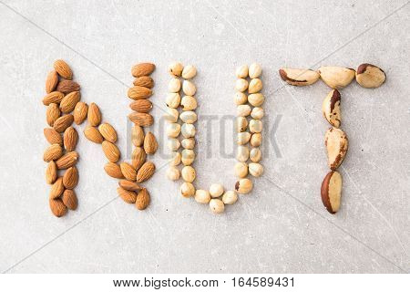Word Nuts Spelled With Various Nuts On Stona Background. Assorted Mixed Nuts