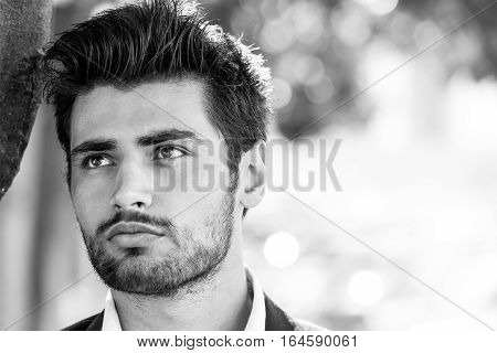 Portrait of a charming and beautiful young man. Blacks hair and perfect face. Outdoor. Black and white