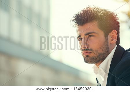 Young handsome man bearded and hairstyle. Hope attitude. He is outdoor with strong day sunlight from behind.