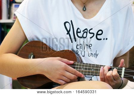 Young teenage playing ukulele. Girl practice a ukulele music
