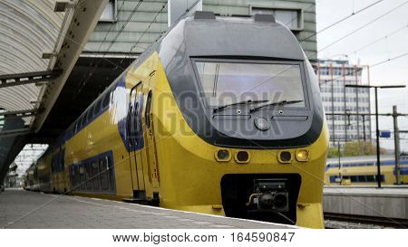 Amsterdam, the Netherlands. Yellow train leaving railway station, wide angle