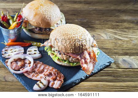 Fresh tasty burger with copy space. Close-up of two homemade burgers sesame buns with succulent beef patties grilled onions bacon and fresh salad served on slate board on a rustic wood table.