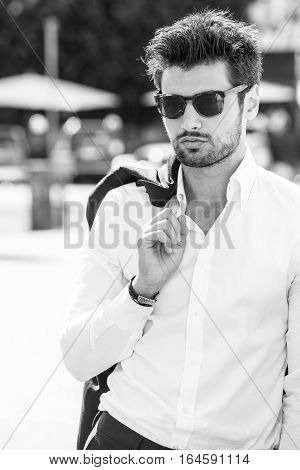 Handsome sexy man outdoors. Elegant and sensual. Sunglasses. legance and beauty. Outdoor. Black and white. The young man wears a white shirt.