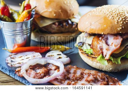 Fresh tasty burger. Close-up of two homemade burgers sesame buns with succulent beef patties grilled onions bacon and fresh salad served on slate board on a rustic wood table.