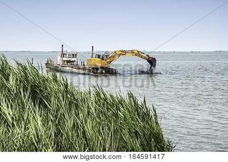 Dredger at work in the delta of the river Po Italy