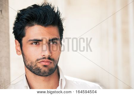Handsome model man portrait. Hope and success. Portrait of a charming and beautiful young man. Blacks hair and perfect face. White shirt.