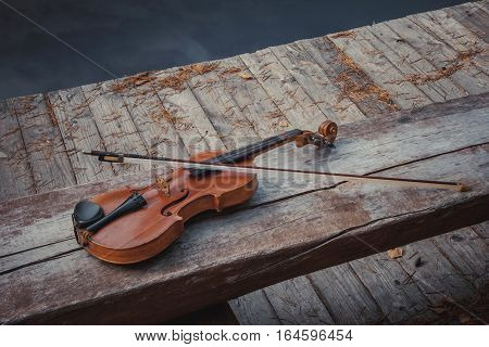 Old violin with a bow lies on a wooden bench