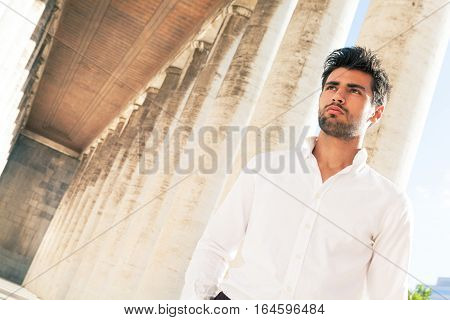 Handsome young elegant man outdoors. Hairstyle and beard. A beautiful Italian man is walking near an ancient colonnade outdoors. His gaze is pensive and thoughtful. White shirt.