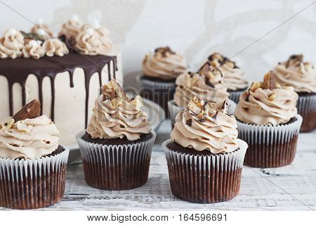 Chocolate cupcake with chocolate mousse cream icing on grunge white wooden background