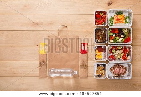 Healthy restaurant food background. Eating right concept. Fresh diet daily meals delivery. Fitness nutrition, vegetables, meat and fruits in foil boxes. Top view, flat lay on wood with copy space