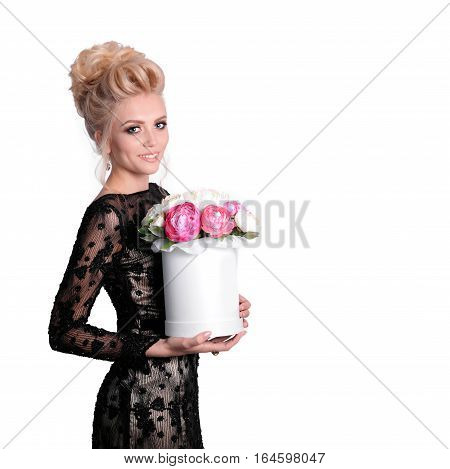 Beautiful blonde woman in elegant black evening dress with updo hairstyle holding a giftbox with bouquet of flowers in her hands. Fashion photo, free space for text