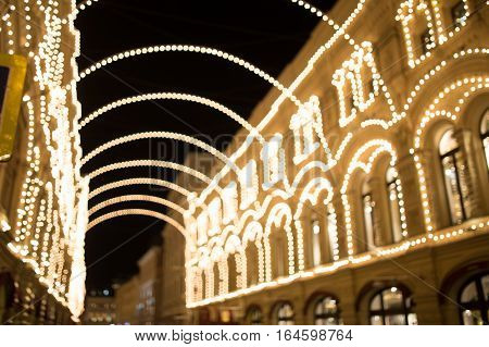 Festive city building with festoons, blurred photo