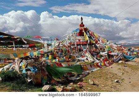 Tibetan ritual stupa and prayer flags with mantras.