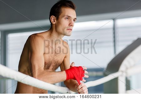 Young sportsman in boxing ring in sports hall