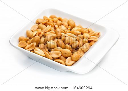 Peanuts in white container on white background. Detailed image taken with macro lens.