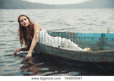 dreamy mysterious blonde girl in a white dress in an old boat on the lake