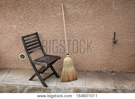 Vintage things: old French garden wooden folding chair and broom. background - yellow pink walls with copper garden tap. Provence. France.