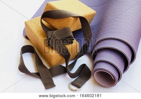 Yoga essentials starter kit for the beginner yogi. Modern lilac mat two cork blocks and grey strap on white background.