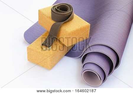 Yoga essentials starter kit for the beginner yogi. Modern lilac yoga mat two cork blocks and grey strap on white background.