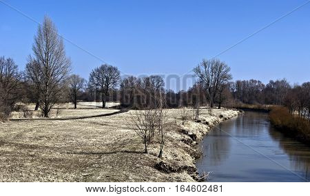 early spring landscape in CHKO Poodri near Jistebnik with meadow, isolated trees without leaves.Odra river and clear sky