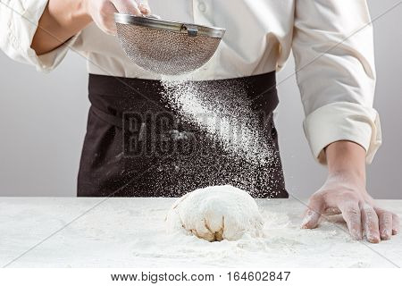 The baker sieving flour and making bread, male hands, kneading a dough, cooking coat