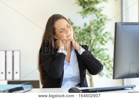 Businesswoman suffering neck pain sitting in a chair while working with a desktop computer in her workplace at office