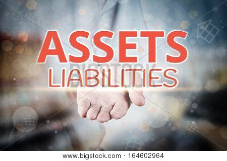 Man Hand Holding Assets Liabilities Text On Blurry Home Icon Property Background.