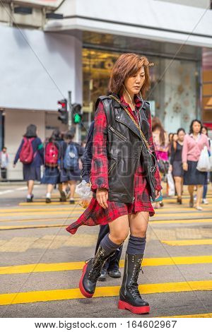Hong Kong, China - December 6, 2016: An asian woman with stylish clothes and smart phones on Yee Wo Street, Causaway Bay, an ultimate destination for travel, fashion and shopping in Hong Kong island.