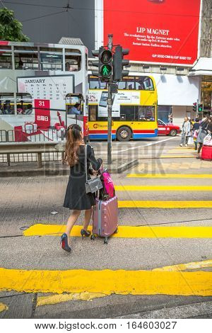 Hong Kong, China - December 6, 2016: An Asian woman with stylish clothes, shopping bags and trolley, crossing Yee Wo Street junction, Causaway Bay, one of the best and the busiest shopping downtown.