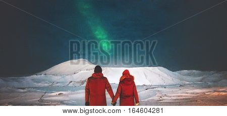 Couple Travelers enjoying Northern lights view above mountains holding hands Travel Lifestyle and love relationship feelings concept vacations into the wild night scene