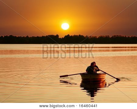 A couple relaxing on a boat at Sunset