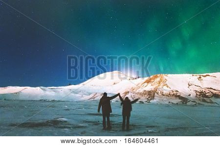 Couple Travelers enjoying Northern lights view above mountains raised hands Travel Lifestyle and relationship man and woman concept vacations into the wild night scene