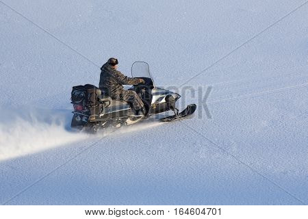 man riding a snowmobile on the smooth snow