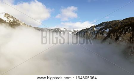 Aerial Drone views over a frozen lake of the french alps