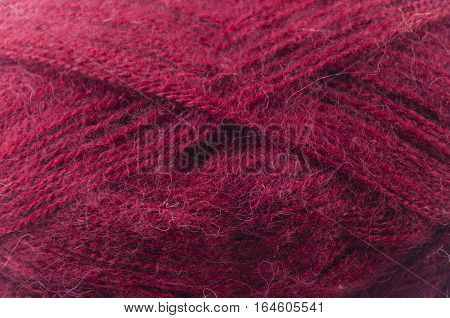 close up of a hank of dark pink yarn for knitting