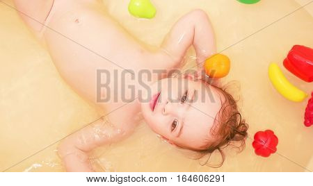 Cute baby girl taking a bath with toys and smile