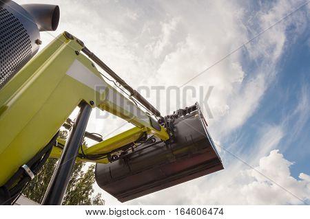 Hydraulic buldozer bucket at construction site against blue sky.
