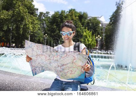 Cheerful woman searching direction on location map while traveling abroad in summer happy female tourist searching road to hotel on atlas in a foreign city during vacation
