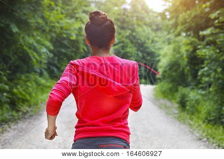 Young lady running on a rural road in the morning