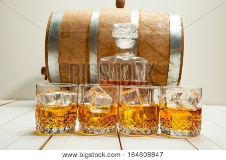 Glass of whisky with ice on old oak barrel