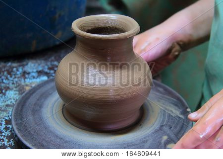 A clay pot on a pottery wheel, pottery craft, moulding the pot with your hands, sculpting hands