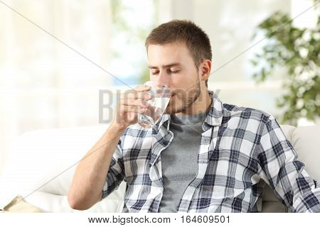 Single man drinking water from a glass sitting on a couch at home