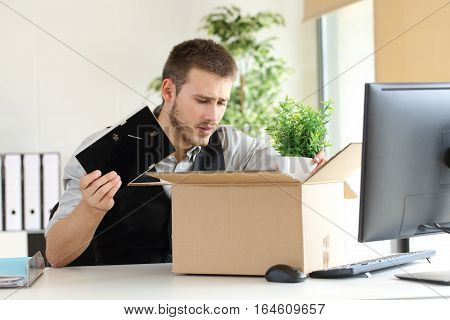 Sad fired businessman putting his belongings in a box from a desktop at office