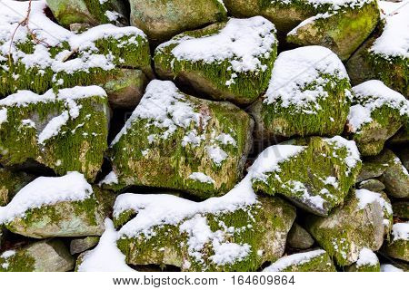 Rocks in a stone wall covered with moss lichen and snow