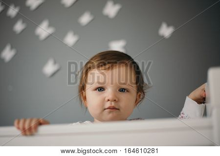 Beautiful, sad little girl indoors portrait in children's room with gray wall and copy space. Baby is nine month old, caucasian. Closeup shot with shallow depth of field. Solitude and sadness concept.