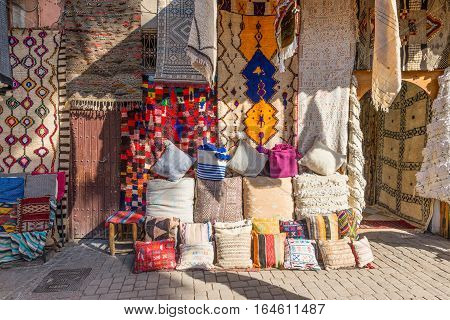 Marrakesh Morocco - December 8 2016: Textiles for sale in the famous souks of Marrakesh Morocco Africa. The sun's rays on the carpets.