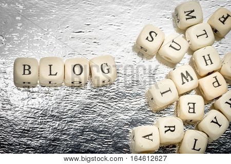 Blog Word On A Wooden Cubes On A Shiny Silver Background With Heap Of Letters