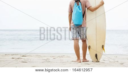 Back Shot Of Young Barefooted Caucasian Surfer Standing On Sandy Beach, Leaning On His Surfboard And
