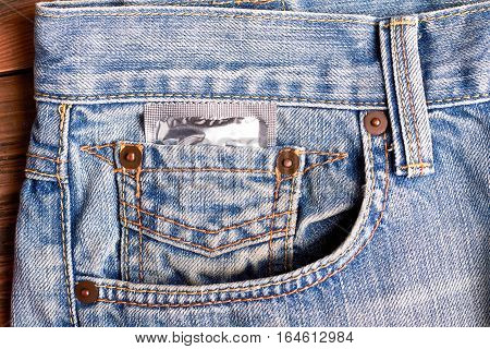 Condom in jeans pocket. Contraceptive in denim. Protect your health.